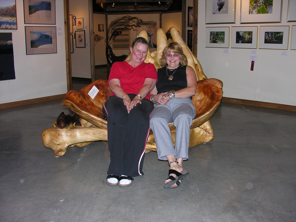 Two women smiling and sitting on a large love seat-shaped sculpture made of wood.