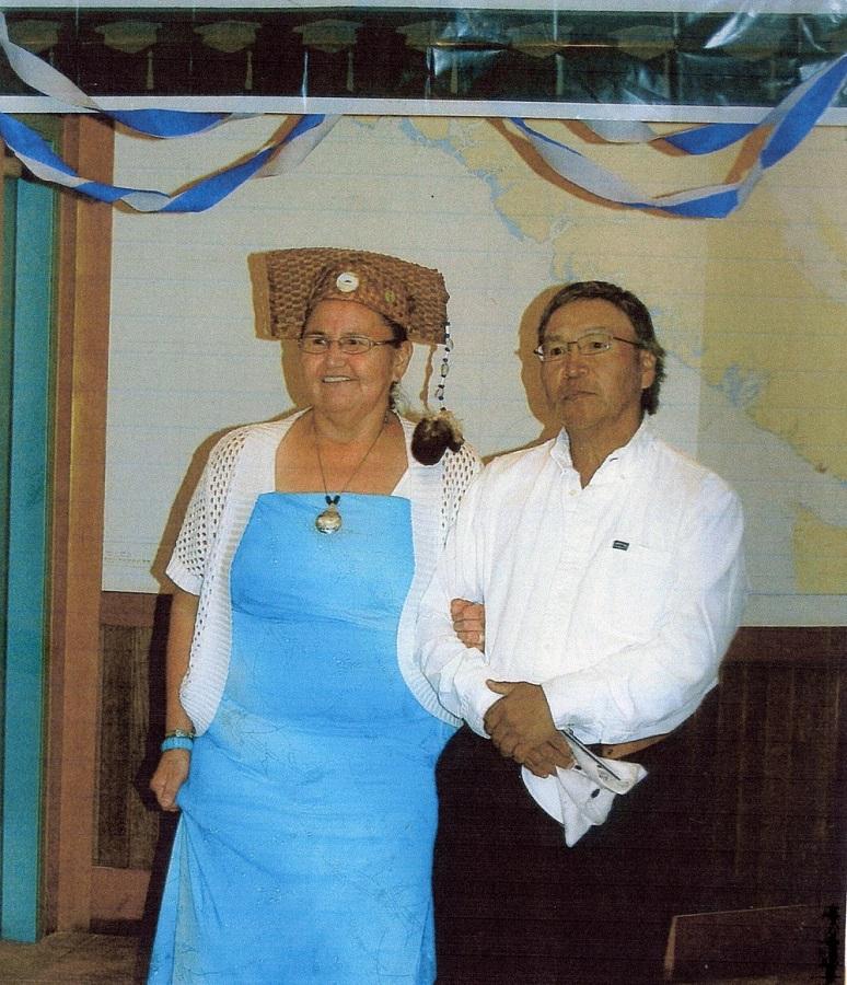 Un homme et une femme, côte à côte. La femme porte un chapeau de remise de diplôme fait d'écorce d'arbre tressée avec un « gland » en fourrure.