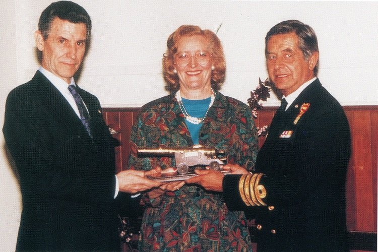 Two men in suits on either side of a woman, presenting her with a ship's cannon.