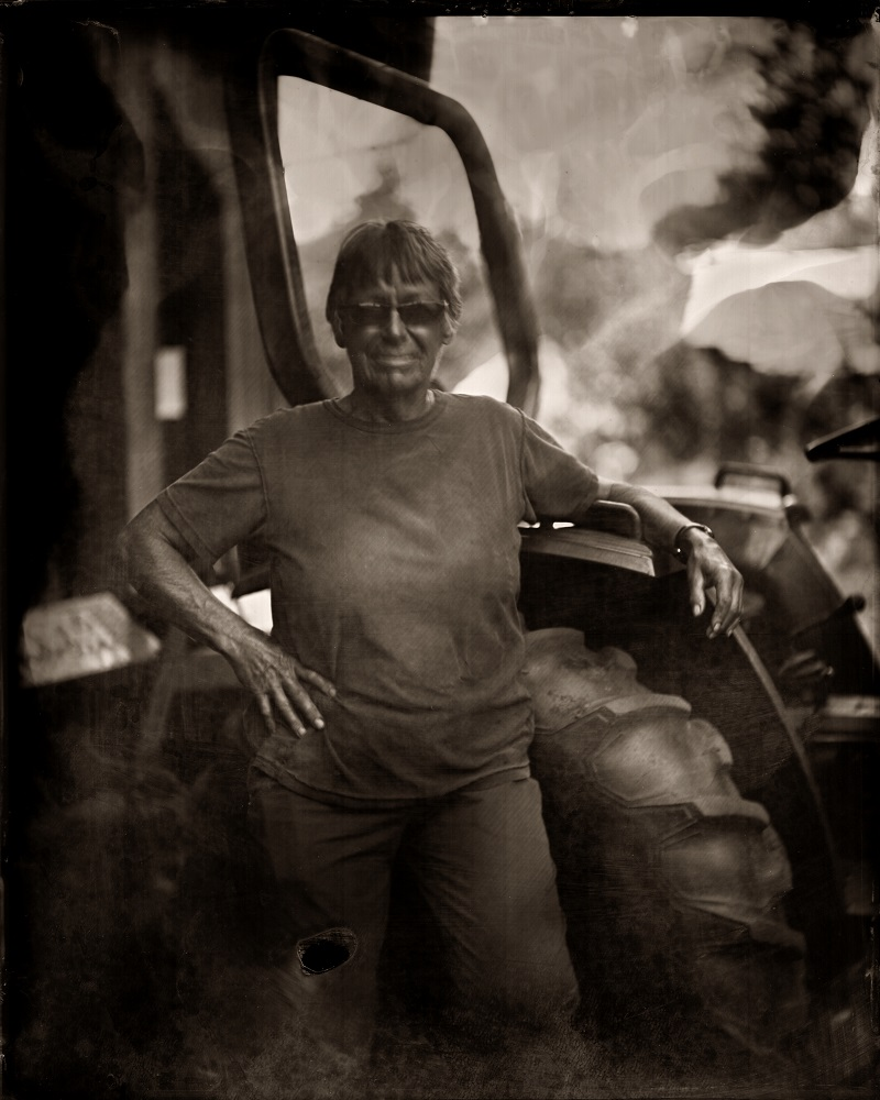 A sepia photograph of a woman standing beside a tractor with her arm resting on the open door.