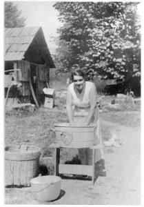 Photographie en noir et blanc d'une femme lavant un vêtement dans une grande cuve à lessive en métal à l'aide d'une planche à laver.
