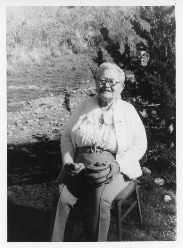 A woman sitting outdoors holding two woven baskets in her lap.