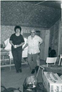 Photographie en noir et blanc de deux femmes debout dans un atelier ou dans un bureau.