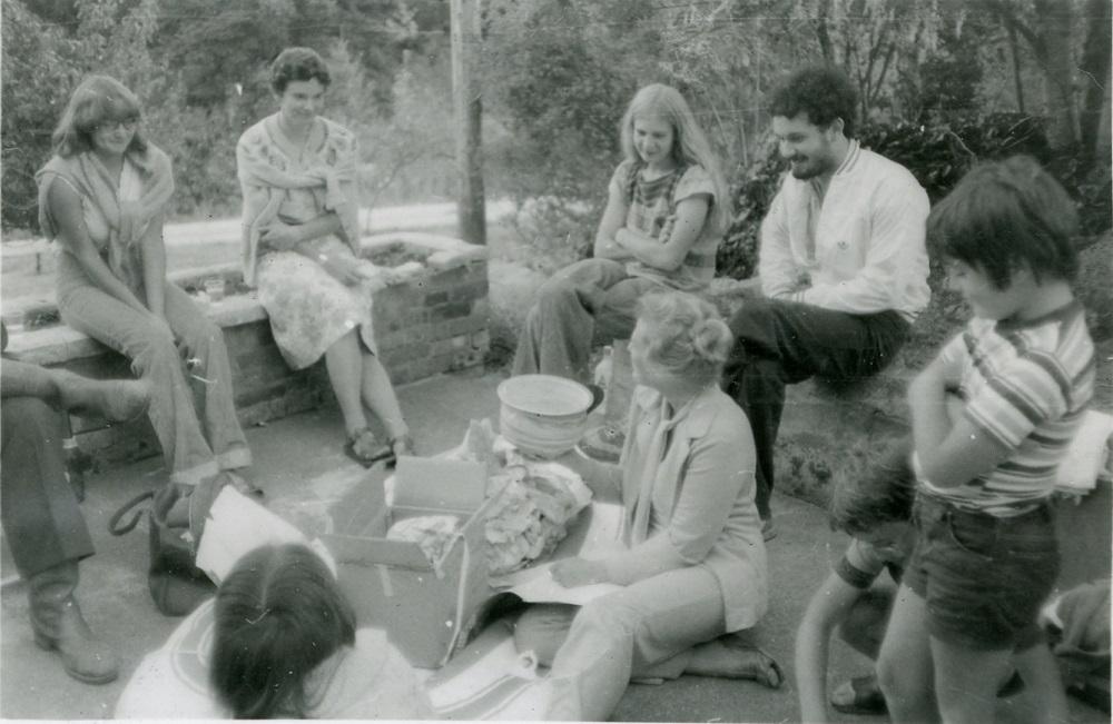 Un groupe d'étudiants assis à l'extérieur, sur le bord de plates-bandes surélevées, autour d'une femme assise au centre.