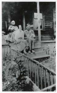 A black and white photograph of a woman in rocking chair at the top of verandah steps with a woman and husband holding a baby sitting on the steps below.