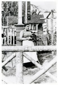A black and white photograph of a woman standing in a yard between a wooden gate and a house.