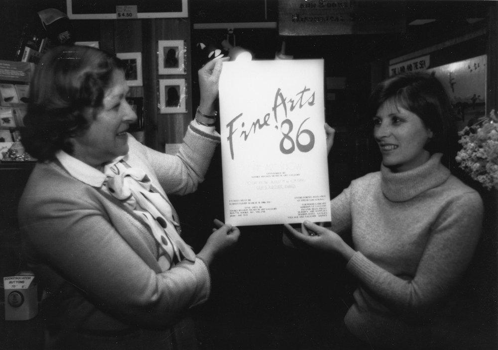 Deux femmes tenant l'affiche de l'Exposition des beaux-arts de Sooke (Sooke Fine Arts Show) de 1986.