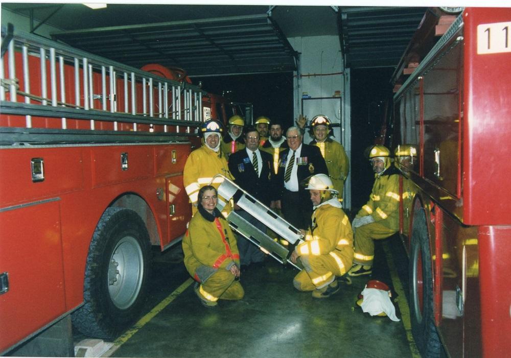 Sept pompiers en tenue de travail et deux hommes en complet portant un insigne, entre deux camions de pompiers.