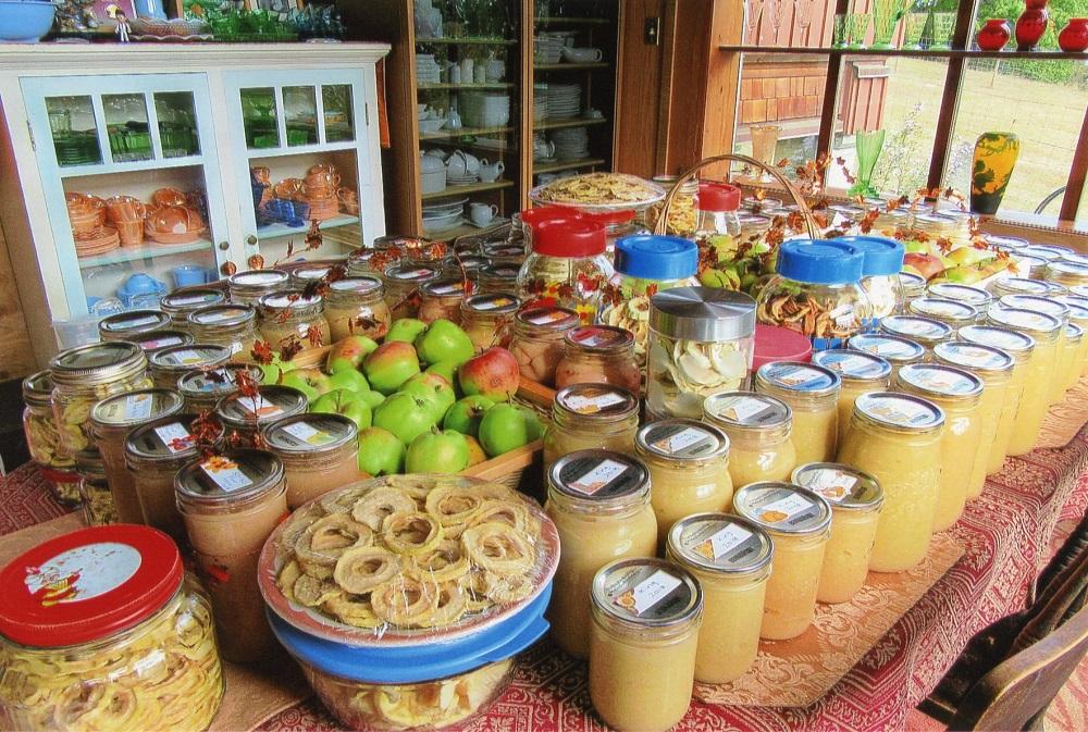 Un assortiment de conserves et de fruits présentés sur une table de ferme.