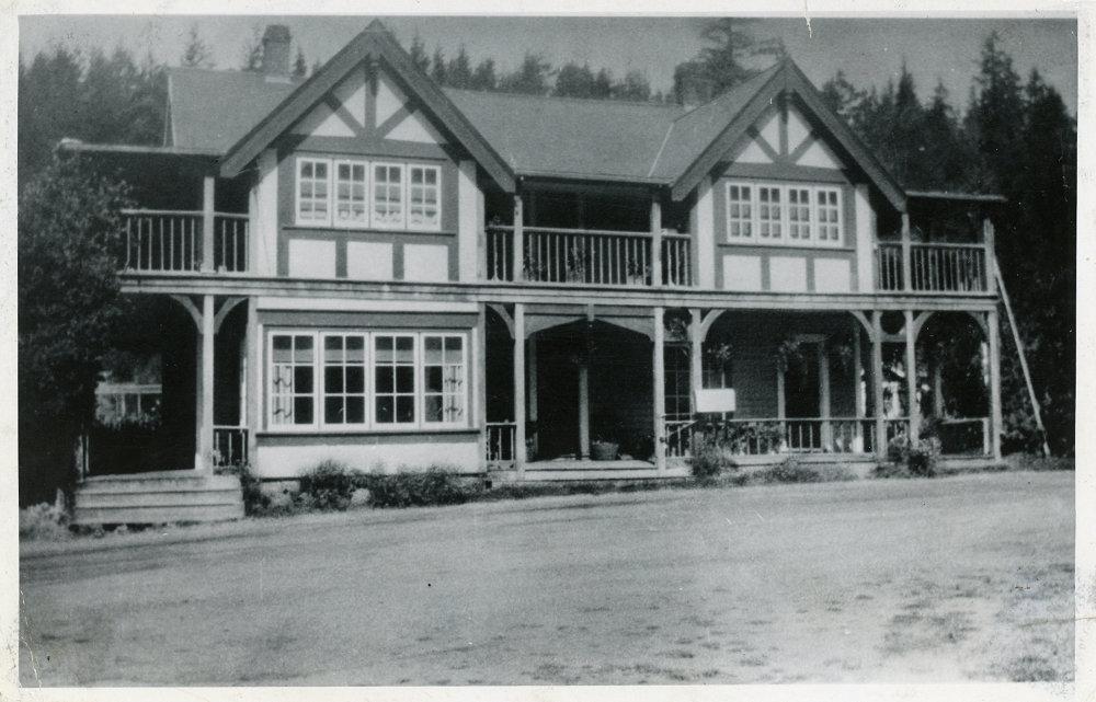 Photographie en noir et blanc d'un bâtiment à deux étages avec balcon et véranda.