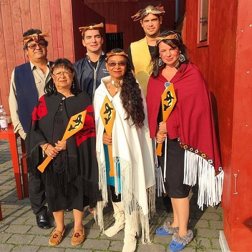 Six people, three men, and three women, standing together dressed in T'Sou-ke First Nations regalia. The three women in the front hold wooden paddles with images of orca whales on them.