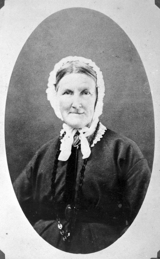 A black and white portrait photo of a woman with a white bonnet.