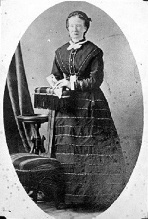A black and white portrait photo of a woman. She wears a high neck blouse with a white neckerchief and a full, striped skirt. Her hands are resting on a cushioned arm rest, and she holds in her hand what appears to be a card.