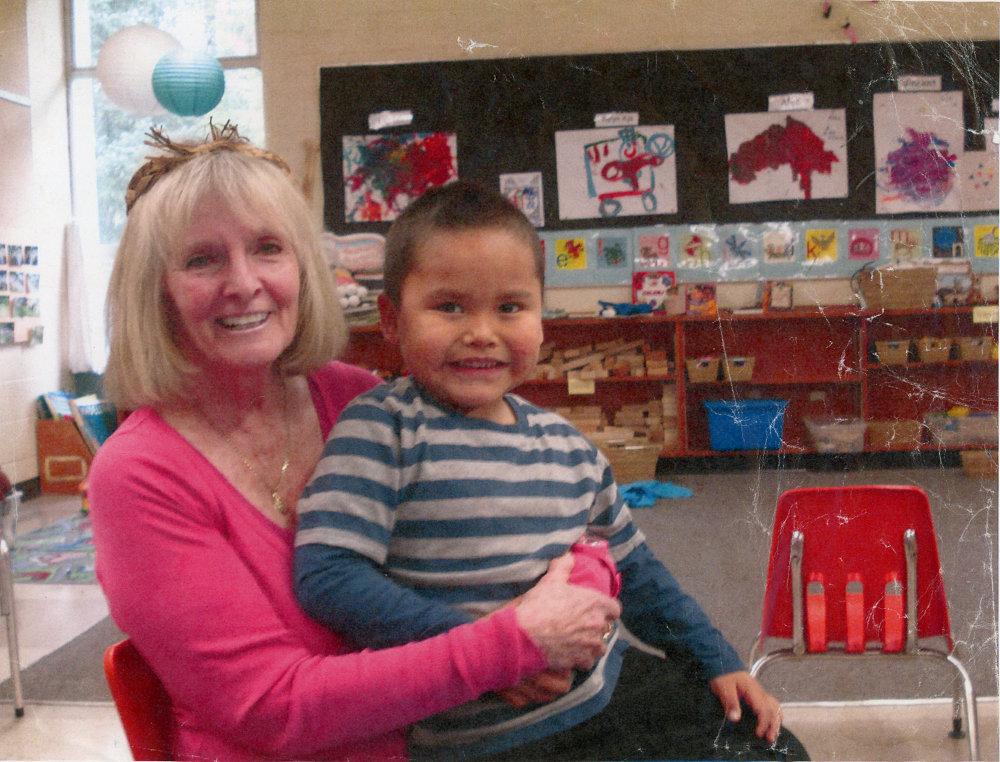 Dans une salle de classe, une femme tenant un petit garçon sur ses genoux. À l'arrière, on voit au mur des peintures faites par les enfants. Il y a aussi des jouets et du matériel d'enseignement dans des paniers.