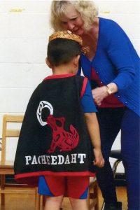 Photo d'une femme ajustant la cape d'un petit garçon. La cape porte le mot « Pacheedaht » et une image d'un loup et de la lune. Le style est caractérisé par les formes et lignes de l'art traditionnel de la côte Nord-Ouest.