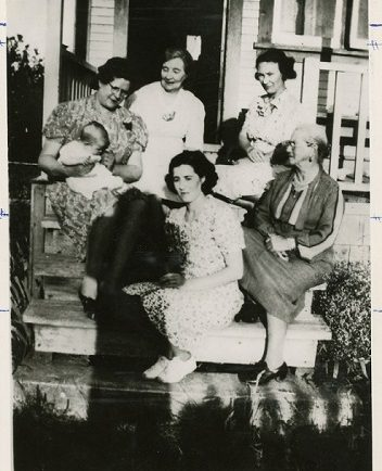 A black and white photograph of different generations of women from one family sitting on a porch together.