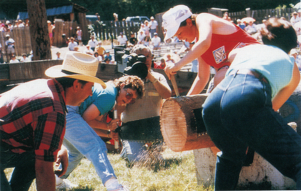 Two women hand bucking a log while a crowd watches. The log is attached with nails to a larger log in a bracket.