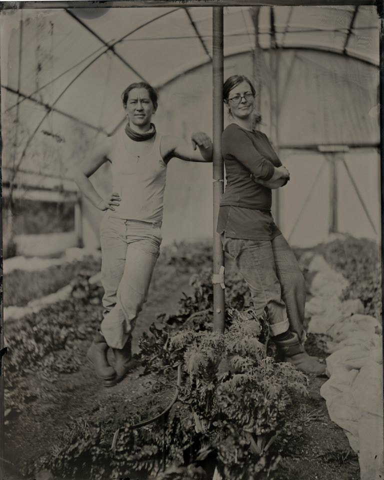 A sepia photograph of two women leaning against a pole in a greenhouse.