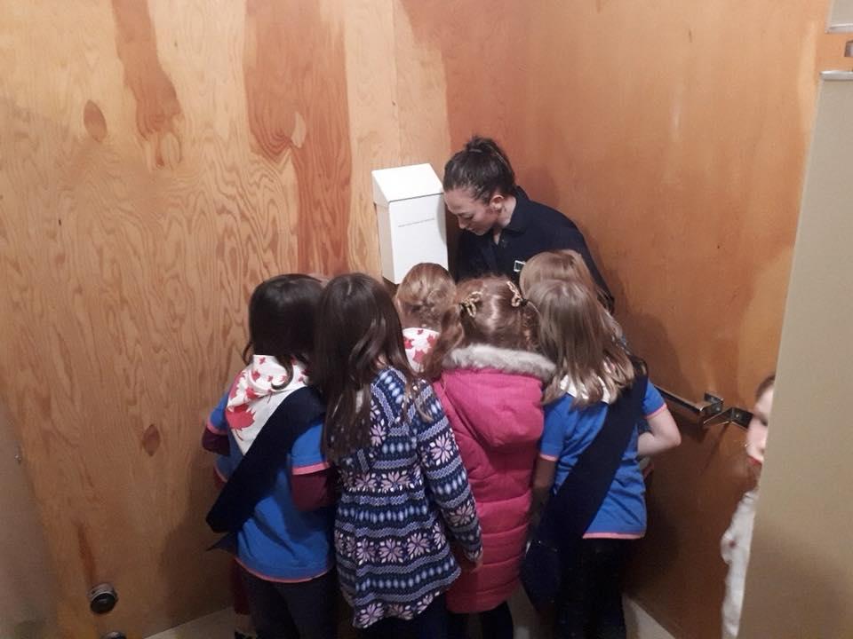 Une femme, entourée de petits enfants, faisant pour eux une démonstration de plomberie.