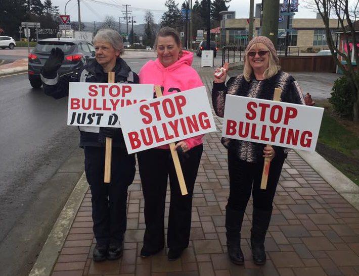 Trois femmes marchant sur un trottoir, tenant des enseignes où on peut lire « Stop Bullying » (Cessez l'intimidation).