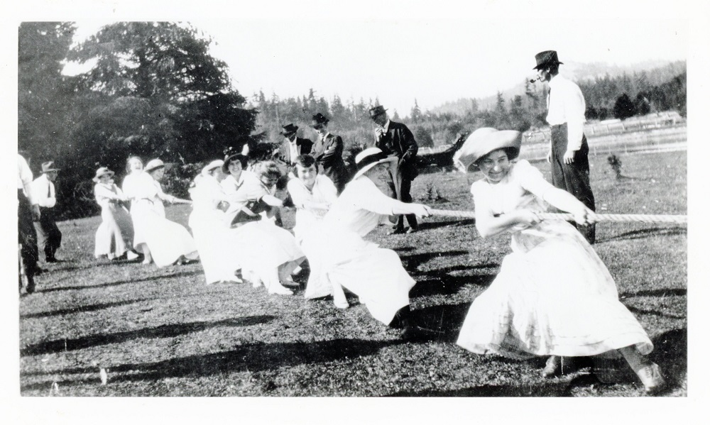 A black and white photograph of several women dressed in dresses and hats pull on a long rope together, smiling.