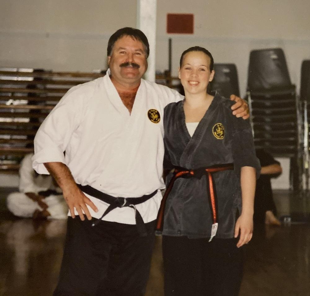Un homme et une jeune femme sont debout côte à côte, en tenue d'arts martiaux. La ceinture de l'homme est noire et celle de la jeune femme est noire avec un liseré (bande centrale) rouge.