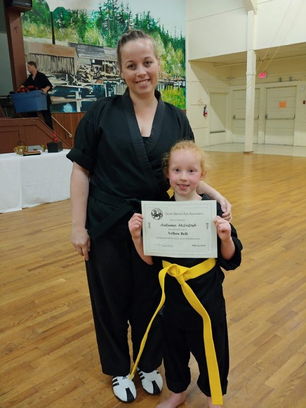 A woman holding the shoulder of her young daughter, who is holding up a certificate for her yellow belt in karate.