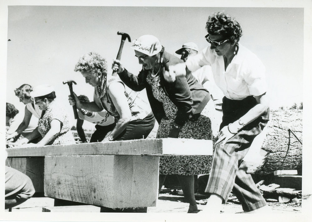A black and white photograph of a line of women with arms raised holding hammers, hammering nails into a piece of wood.