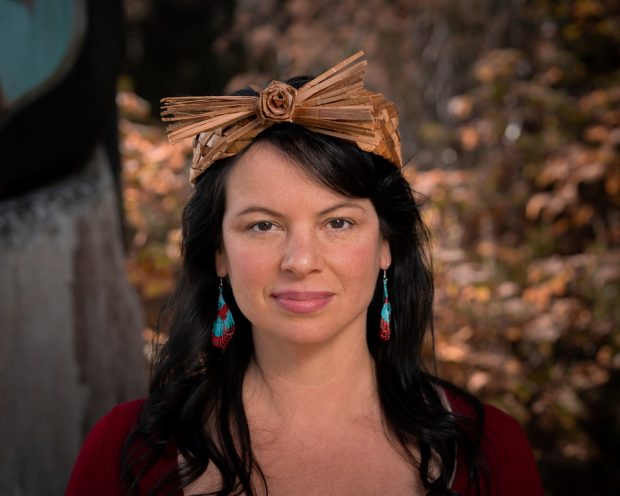 Portrait photo of a woman wearing a traditional woven cedar headband.