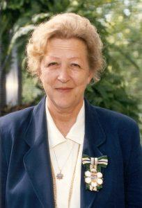 Portrait photo d'une femme portant à son revers un insigne représentant une fleur de cornouiller stylisée sous une boucle de ruban vert, or, blanc et bleu.