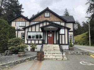 Une grande maison à plusieurs niveaux, sur une rue en pente, des marches menant à la porte d'entrée rouge.