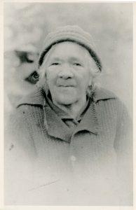Portrait photo en noir et blanc d'une femme âgée portant un bonnet et un chandail tricotés.