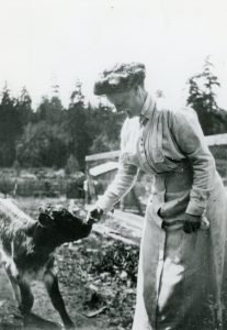 Photo en noir et blanc d'une femme nourrissant un veau élevé sous la mère à l'extérieur.