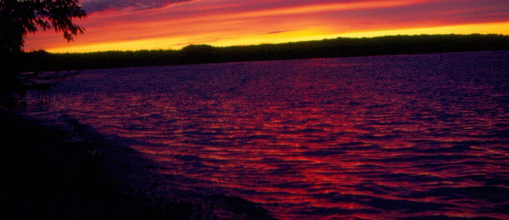 Colour photo of a body of water at sunset, sky displays yellow, orange, and purple hues, the water appears purplish.