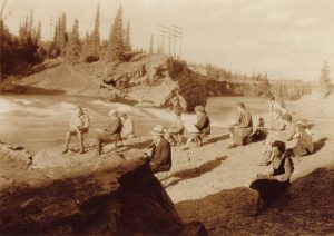Sepia photo of group of artists sketching on bank of river in treed and rocky landscape.