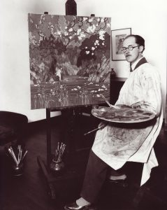 Black and white photo of man in white smock, holding paintbrushes and palette, sitting next to easel with painting of girl next to river.