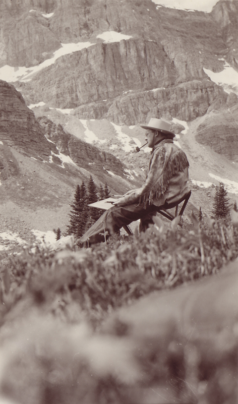 Black and white photo of man wearing fringed buckskin jacket, hat and smoking pipe, painting in a mountain landscape.