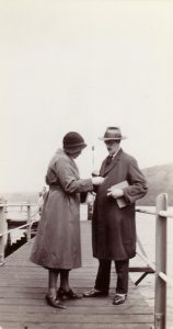 Black and white photo of sharply dressed couple standing on dock, consulting something in woman's hand.