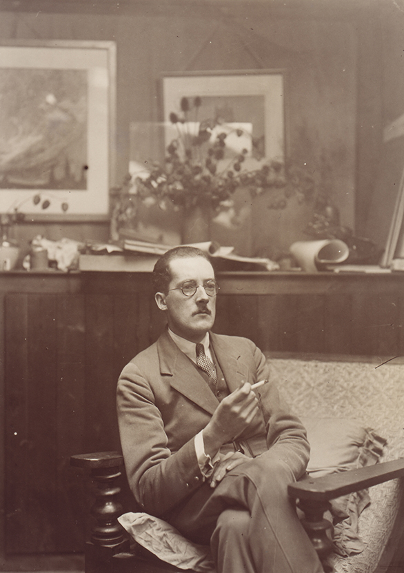 Sepia portrait of man with moustache seated in wood panelled room, wearing glasses, suit and tie, and smoking cigarette. Paintings on wall.