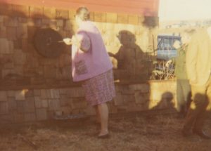 Colour photo of woman facing away, with branding iron in hand, branding circular object on outdoor wall.