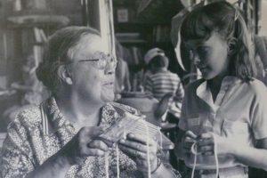 Photo noir et blanc d'une femme qui tisse avec une jeune fille sur un métier à tisser en carton.