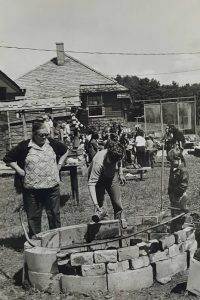 Black and white photo of two adults and one child around fire pit with old fashioned schoolhouse behind.