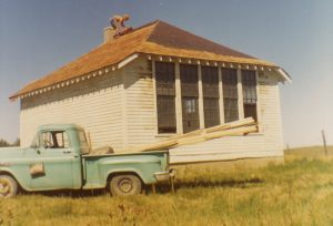 Colour photo of man roofing an old-fashioned white schoolhouse with green pickup-truck in front.