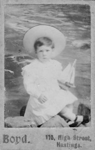 Black and white studio portrait of young boy holding toy boat and wearing large hat and white dress.