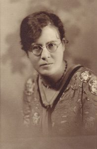 Sepia studio portrait of young woman in glasses.