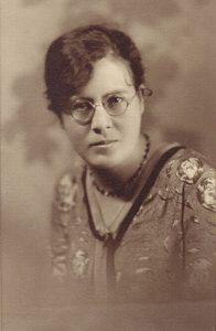 Portrait de studio sépia d'une jeune femme portant des lunettes.