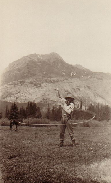 Sepia photo of man in hat with lasso standing in front of mountain and horse in distance.
