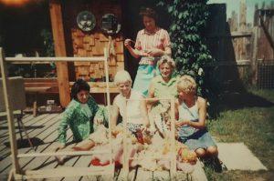 Photo couleur de cinq femmes sur une terrasse avec des piles de laine brute et deux métiers à tisser