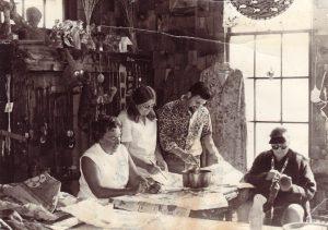 Photo noir et blanc de trois femmes et d'un homme travaillant dans un atelier d'art rempli de textiles et de céramiques; fenêtre lumineuse derrière.