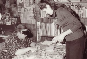 Black and white photo of woman working at a table with younger woman student standing opposite; bookshelf and art supplies behind.